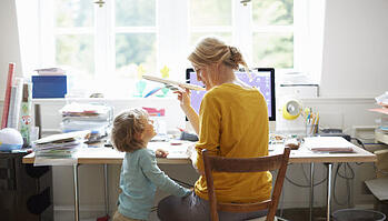 Woman at computer working from home and playing with young child