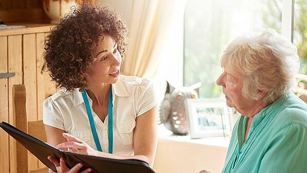 home-healthcare-nurse-reviewing-info-with-senior-patient-page